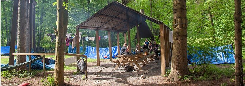 Bivakterrein met overkapping en overdekte kampvuurplek om te kamperen naast een beekje